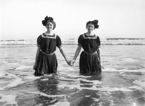 Two young women hold hands in the surf, ca. 1905.